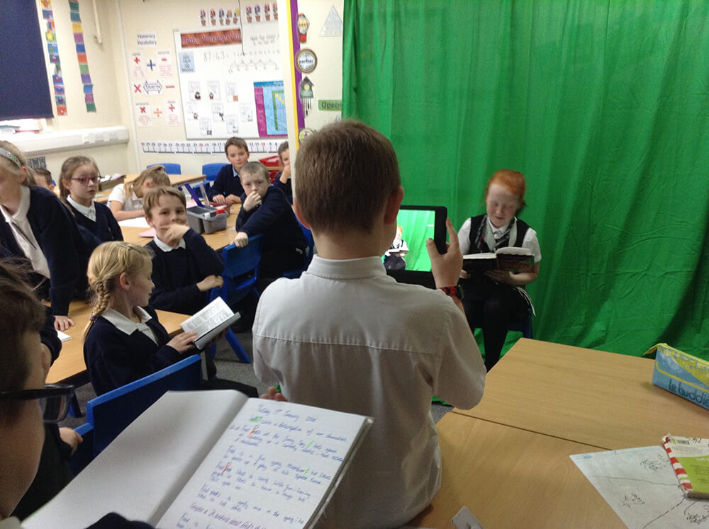 Students filming with a green screen background