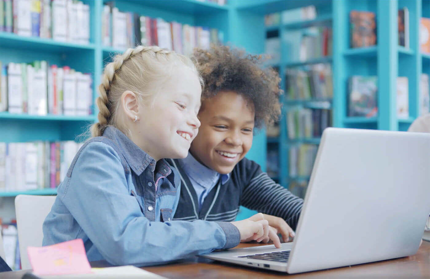 Two students smiling while using a laptop in a library